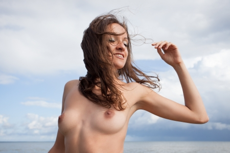female nudity: Young nude woman with hair flying against the sea background