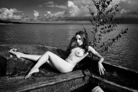 mujer desnuda sentada: Joven mujer desnuda sentada en un barco sobre el fondo del mar