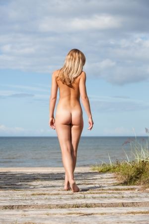 nude nature: Young nude woman goes to the sea to get a tan