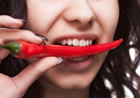 Young lady holding red hot chili pepper in mouth. Focus on lips photo