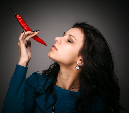 young lady holding red hot chili pepper in mouth photo