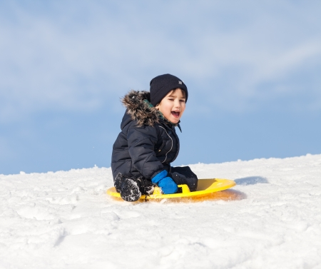 Boy on sleigh. Sledding at winter time