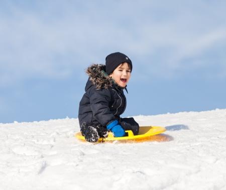 Jongen op slee. Rodelen in de winter Stockfoto