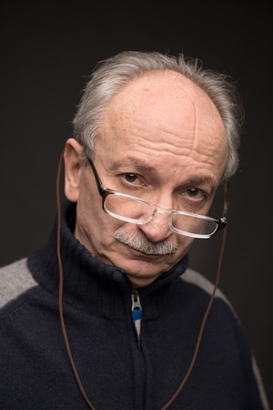 skeptic: An elderly man with glasses looks skeptically on a dark background