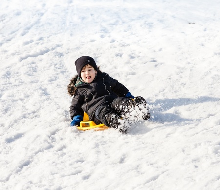 sledging people: Boy on sleigh. Sledding at winter time