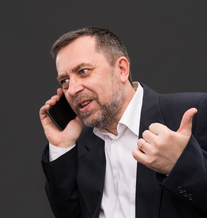 Handsome middle-aged business man speaks on a mobile phone and gesturing photo