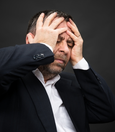 Headache. Portrait of an elderly man with face closed by hands Stock Photo