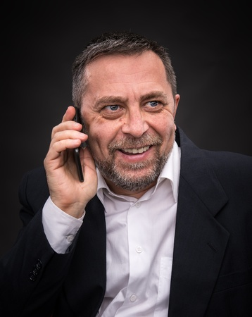 Smiling middle-aged businessman speaks on a mobile phone and gesturing photo