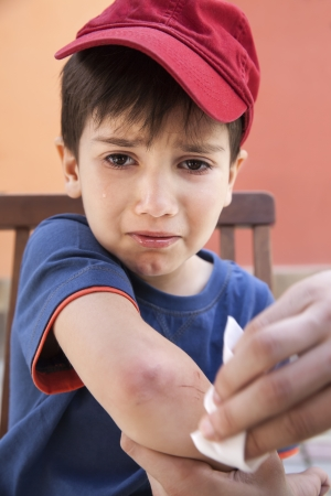 injuring: Small boy crying in pain injuring his hand and his father provides first aid