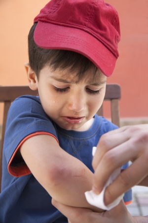 injuring: Small boy crying in pain injuring his hand. Father provides first aid Stock Photo