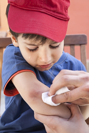 Small boy crying in pain injuring his hand and his father provides first aid photo