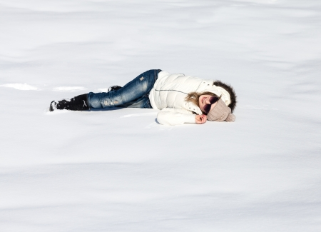Young woman lying in snow enjoying a sunny winter day photo
