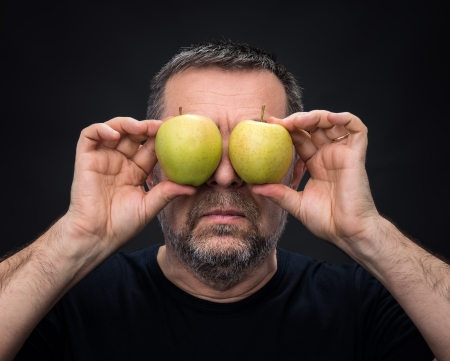 Middle-aged man in black with two green apples instead of eyes photo