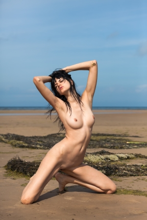 Young fully nude woman posing on the beach