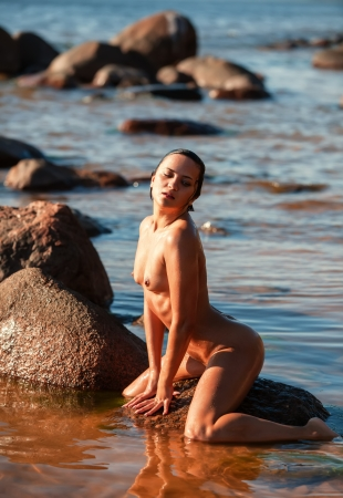 Young nude woman sitting on stone  against the sea background photo