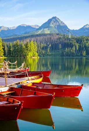 sunrise lake: Red boats in mountain lake in High Tatra. Strbske pleso, Slovakia, Europe. Focos on boat