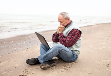 Old man sitting with notebook on beach photo