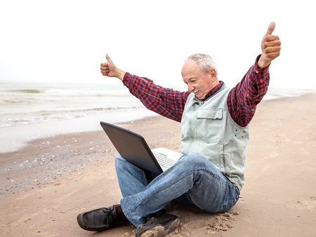 All OK! Old man sitting with notebook on beach photo