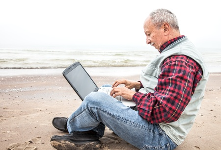 Old man sitting with notebook on sea beach photo