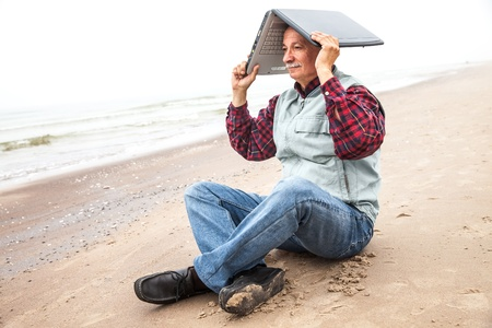 Old man sitting on a sea beach and holding a laptop on his head on a foggy day photo