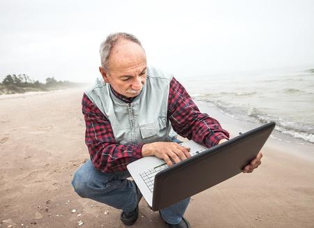Senior businessman on beach working with notebook photo