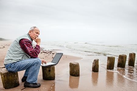 Senior zakenman op strand werken met een notebook