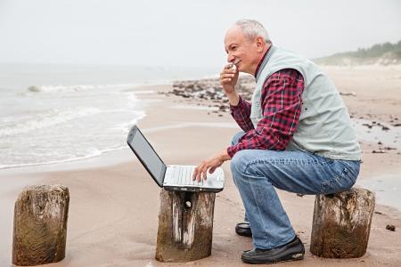 Hombre de negocios mayor en la playa trabaja con el cuaderno Foto de archivo - 21361879