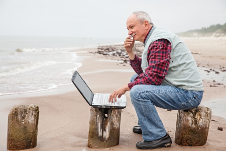 Senior businessman on beach working with notebook Stock Photo
