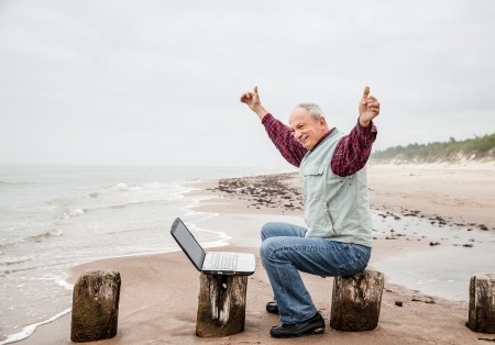 Happy old man with a laptop on the beach on a foggy day photo