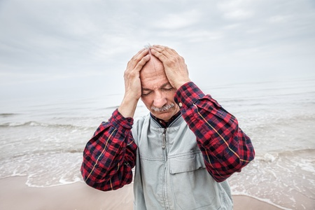 Elderly man suffering from a headache on sea background on foggy day photo