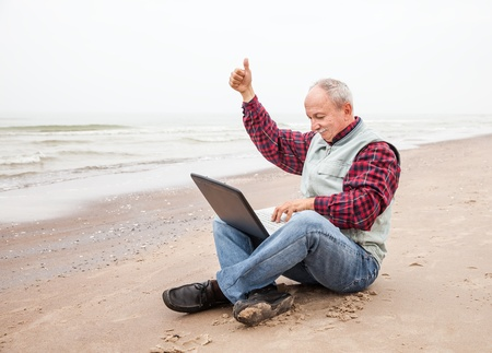 Happy old man sitting with notebook on beach photo