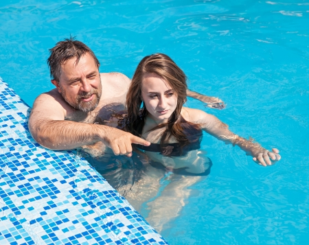 Happy family. Father and daughter swimming in the pool on a sunny day. photo