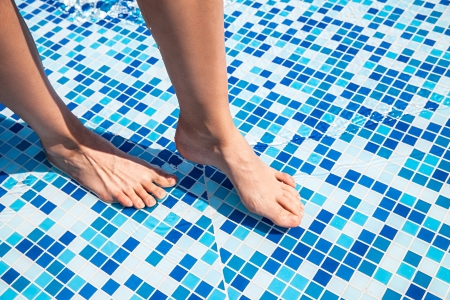 wet floor: Overhead view of womans legs in pool at luxury resort Stock Photo
