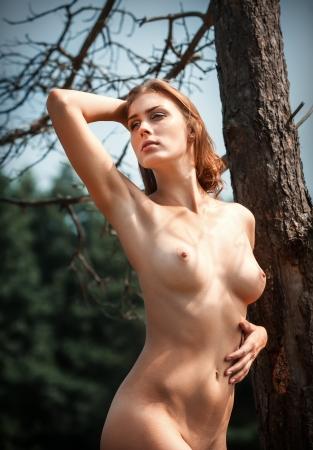 Hermosa joven al aire libre mujer desnuda. Disfrute de la naturaleza. Se encuentra cerca de un viejo �rbol Foto de archivo - 21872142