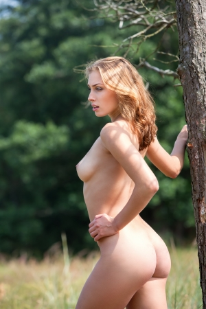 bare breast: Beautiful Young Naked Woman Outdoors. Enjoy Nature. Stands Near An Old Tree Stock Photo