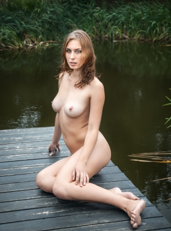 bare breasts: Beautiful young naked woman outdoors. Enjoy nature near a small pond Stock Photo