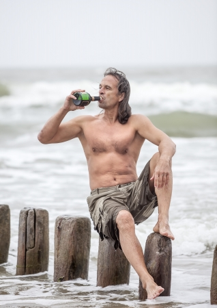 Middle-aged man sitting near the sea and drinking alcohol Stock Photo
