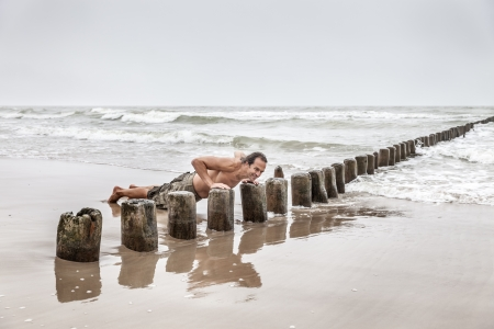 Middle-aged man doing pushups on the beach photo