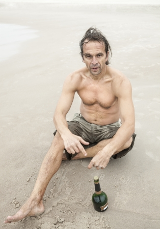 Middle-aged man sitting on the sand near sea and drinking alcohol photo