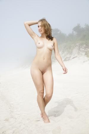 nudo di donna: Giovane donna nuda che cammina lungo una spiaggia di sabbia in una giornata nebbiosa