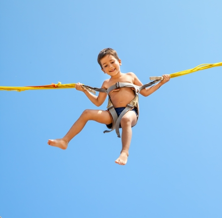 Little boy jumping on a trampoline on blue sky background