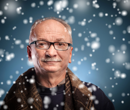 x-mas, winter, happiness concept - smiling  elderly man looks skeptically photo
