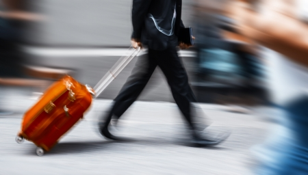 intentional: Businessman with a red suitcase in a hurry. Intentional motion blur
