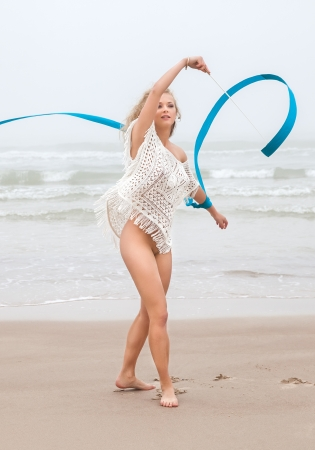 Young beautiful gymnast woman dance with ribbon on the beach at foggy day photo