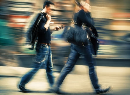 Hot day in the city. Man and woman talking on a cell phone in a hurry. Intentional motion blur and color shift Stock Photo
