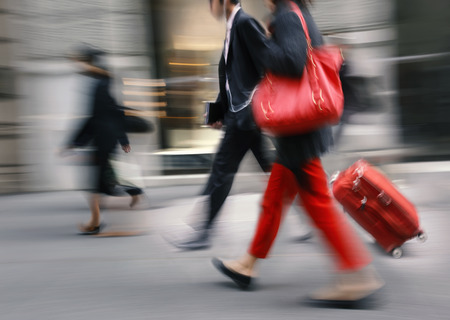 People with a red bag and a suitcase walking down the street. Intentional motion blur photo