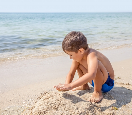 A caucasian child boy playing with sand in the beach photo