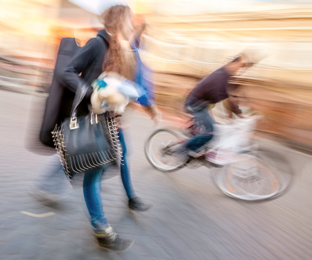 Young people and cyclist going about their business. Street scene with intentional motion blur.