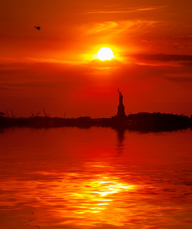 The Statue of Liberty and the setting sun with water reflection photo