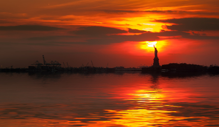 Statue of Liberty silhouette and the setting sun with water reflection